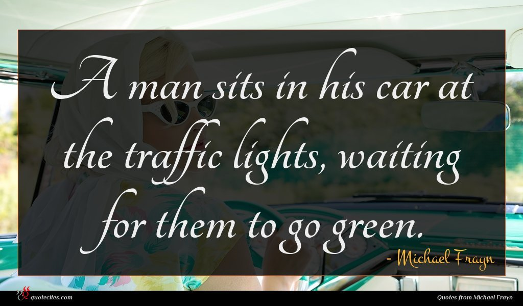 A man sits in his car at the traffic lights, waiting for them to go green.